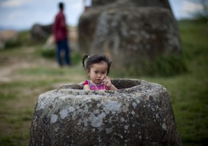 Flicka sitter i en kruka på Plain of Jars